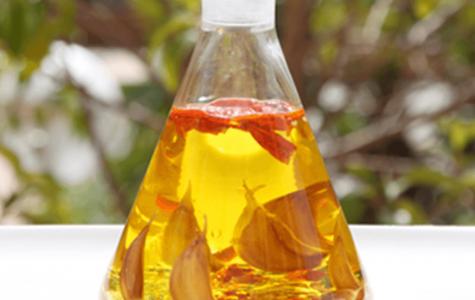 Aceitera con aceite de oliva, ajos y guindillas en mesa blanca y al aire libre