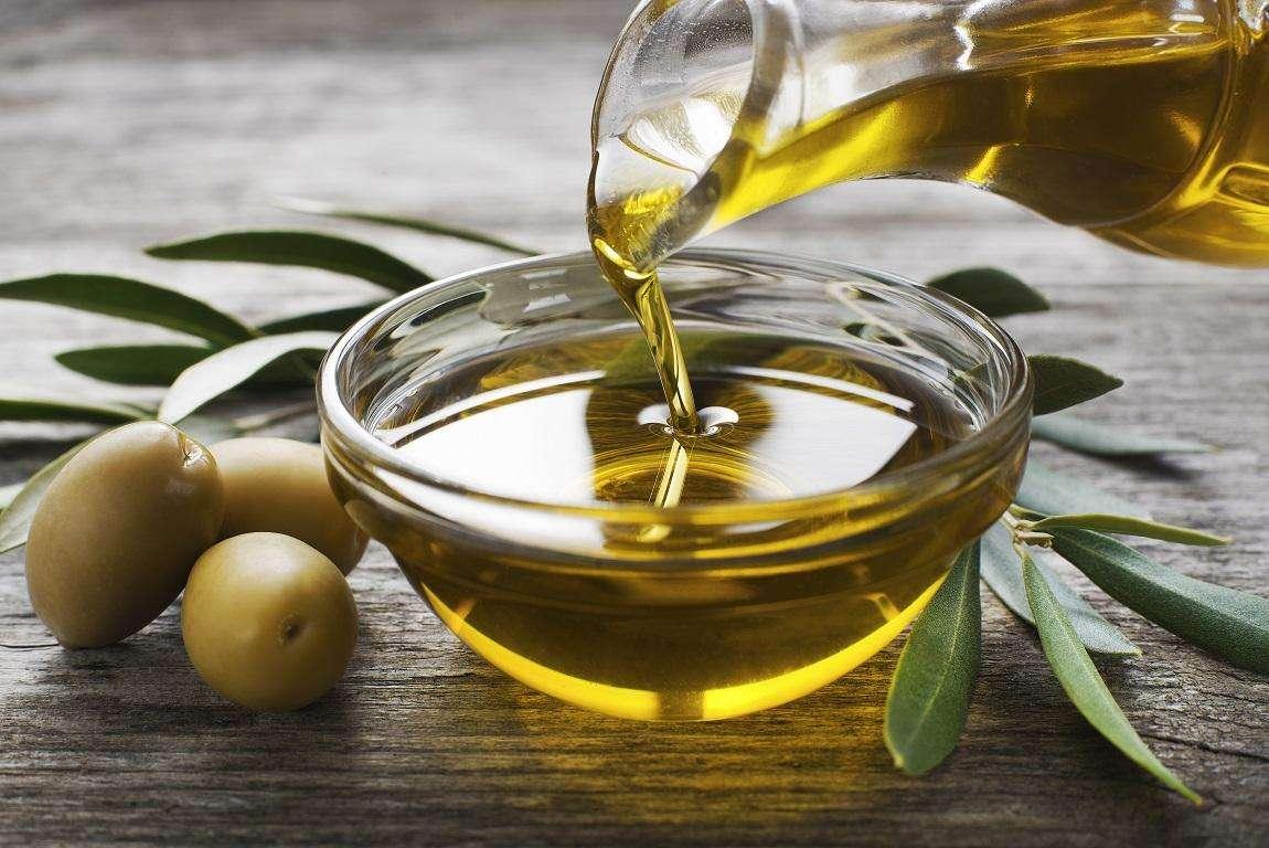 cuenco de aceite de oliva acompañado de frasca de cristal