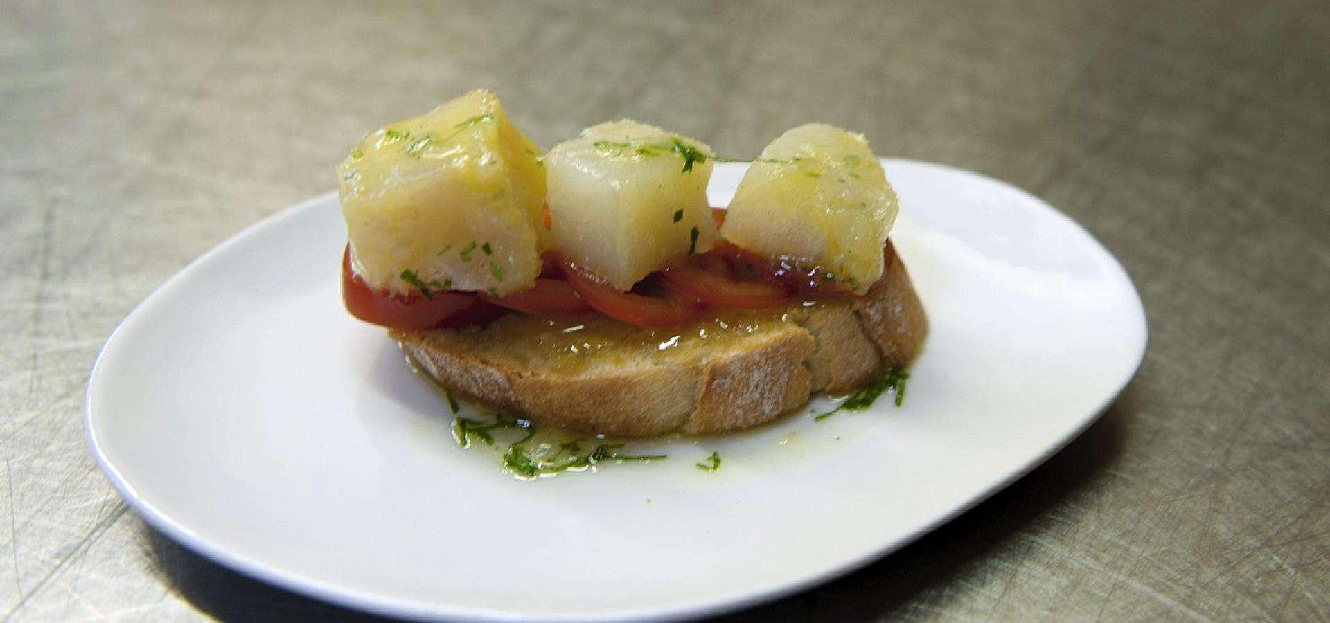 montadito con bacalao ahumado, tomates cherry, albahaca y puré de aceitunas negras