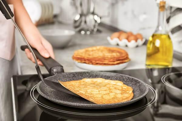preparando en la cocina unas tortitas con aceite de oliva en la sarten caliente
