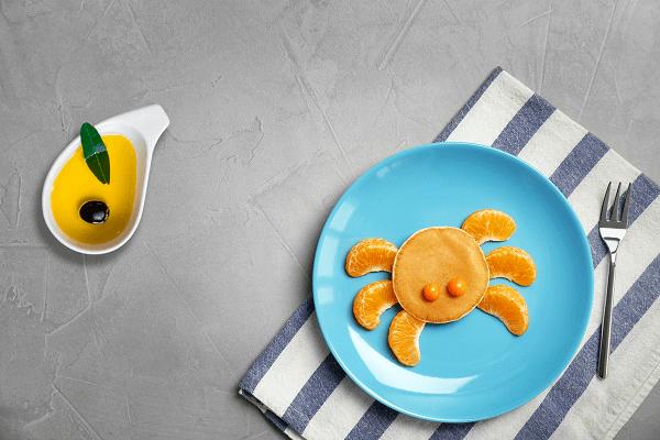 Tortitas con aceite de oliva y gajos de mandarina con divertida forma de cangrejo