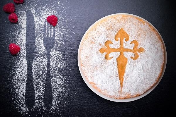 Tarta de santiago sobre pizarra decorada con azúcar glass y frutos rojos